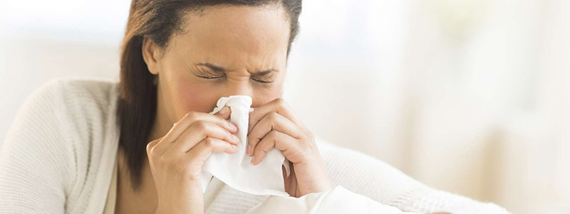 Young woman blowing nose with tissue at home
